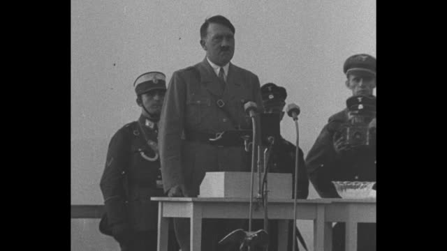 hitler stands at small wooden table with microphones men in paramilitary uniforms stand behind him - adolf hitler stock-videos und b-roll-filmmaterial