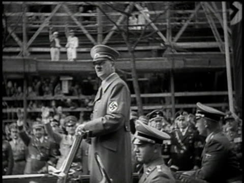 Hitler stands in moving car and salutes crowd amid Nazi paraphernalia / Sudetenland Czechoslovakia
