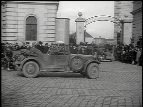 stockvideo's en b-roll-footage met hitler's motorcade arriving in vienna driving under arched gate while crowd watches and someone waves / austria - 1938