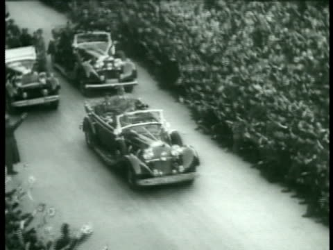 stockvideo's en b-roll-footage met hitler's motorcade crowd lining street people widely waving cheering ha ws nazi banners hanging from building hitler on balcony in uniform no hat... - 1938