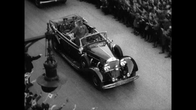hitler's motorcade crowd lining street people widely waving cheering nazi banners hanging from building / hitler on balcony in uniform no hat... - adolf hitler video stock e b–roll