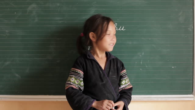 a hmong student smiles and uses chalk to write on a chalkboard. - young girls stripping stock videos and b-roll footage
