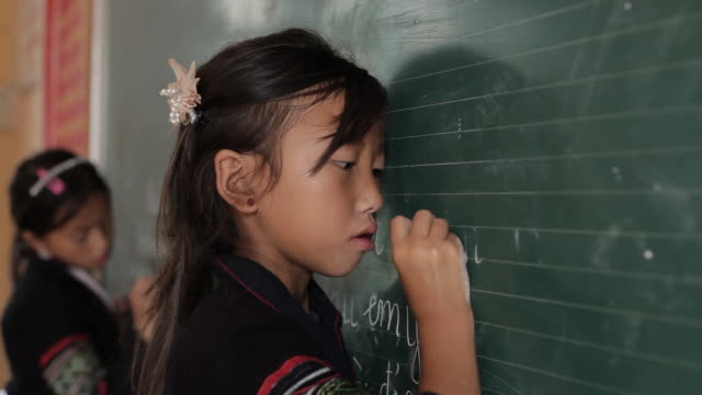 A Hmong student uses her hand to erase characters on a chalkboard.