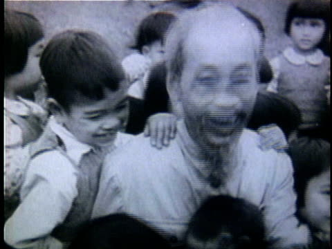ho chi minh being embraced by adoring children as he comes out of building / north vietnam - ゴーティー点の映像素材/bロール