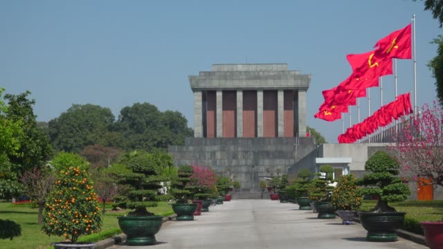 ho chi minh mausoleum at hanoi, vietnam. red communist and vietnamese flags waving - russian flag stock videos & royalty-free footage