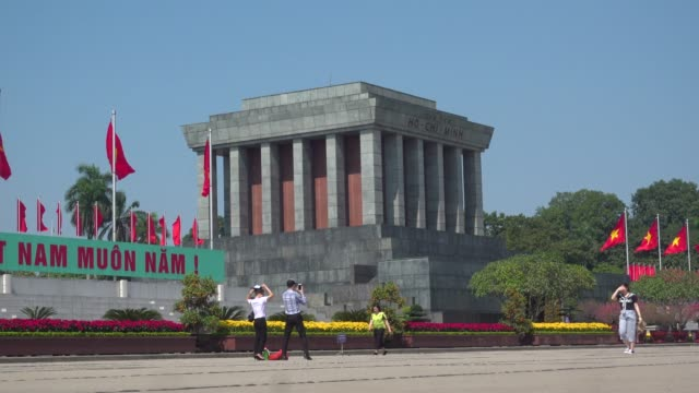 ho chi minh mausoleum at hanoi, vietnam. tourist taking pictures and walking along the big square. red communist and vietnamese flags waving - waving icon stock videos & royalty-free footage