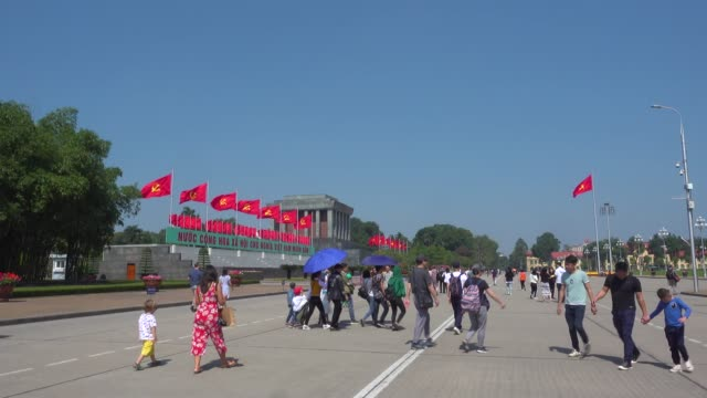 ho chi minh mausoleum at hanoi, vietnam. tourist walking along the big square. red communist and vietnamese flags waving - waving icon stock videos & royalty-free footage