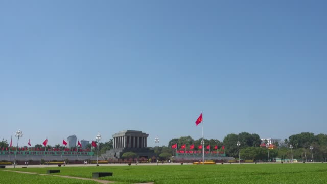 ho chi minh mausoleum at hanoi, vietnam. wide angle shot with copy space. tourist walking along the big square. red communist and vietnamese flags waving - waving icon stock videos & royalty-free footage
