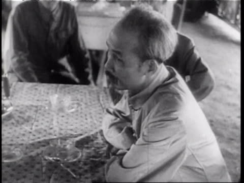 Ho Chi Minh sitting at table and talking with others smiling Ho Chi Minh during Vietnam War on August 01 1965 in Vietnam