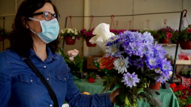 市場で花を買うコロナウイルスパンデミック成熟した女性の趣味と余暇 - フローリスト点の映像素材/bロール