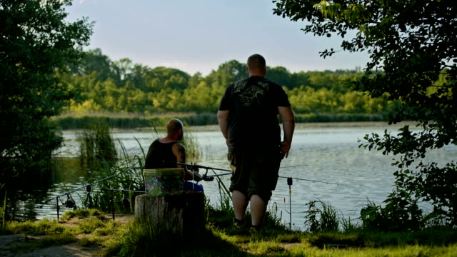 hobby fishermen relaxing and angling at a lake in a nature reserve near berlin - tattoo stock videos & royalty-free footage