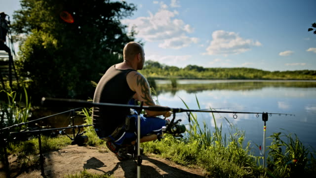 Hobby fishermen relaxing and angling at a lake in a nature reserve near Berlin