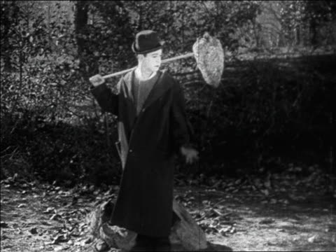 b/w 1925 hobo (harry langdon) carrying beehive on stick / takes it off + looks at it / feature - 1925 stock videos & royalty-free footage