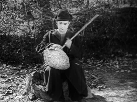 B/W 1925 hobo (Harry Langdon) sitting down with large beehive in lap / feature