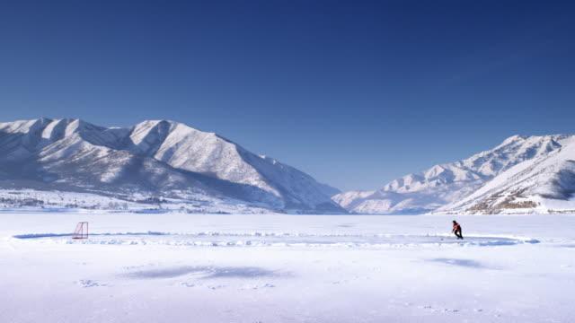 vídeos de stock e filmes b-roll de hockey player on a frozen lake. - pista de patinagem no gelo