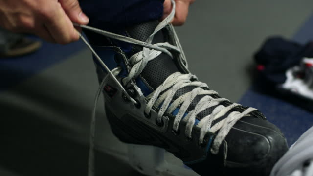 cu of hockey player tying a skate - tie stock videos & royalty-free footage
