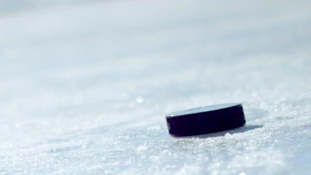hockey puck falling onto ice and being picked up by a gloved hand. - hockey glove stock videos & royalty-free footage
