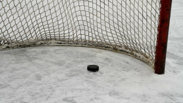 hockey pucks slide into empty net - ice rink stock videos & royalty-free footage