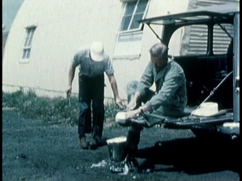 1963 montage hog farm workers clean and disinfect footwear to prevent spread of hog cholera virus / united states - abbürsten stock-videos und b-roll-filmmaterial