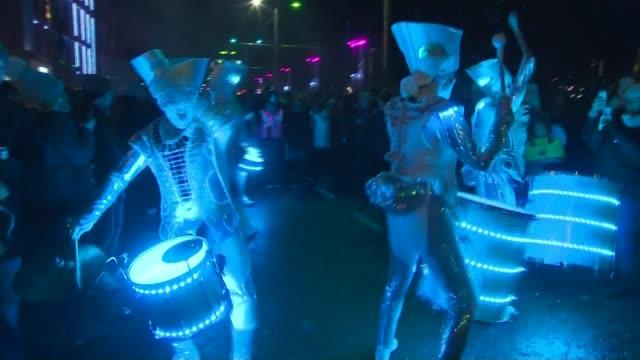 Hogmanay celebrations in Edinburgh SCOTLAND Edinburgh EXT / NIGHT **Music heard SOT** Illuminated drummer performers along past crowd Giant puppets...