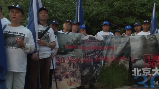 holding aloft banners and battery powered candles activists rally in front of the chinese embassy in washington to commemorate the 30th anniversary... - tiananmen square stock videos & royalty-free footage