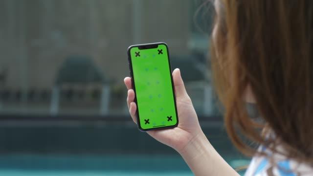 vídeos de stock, filmes e b-roll de segurando chroma key tela verde smartphone assistindo conteúdo - portable information device
