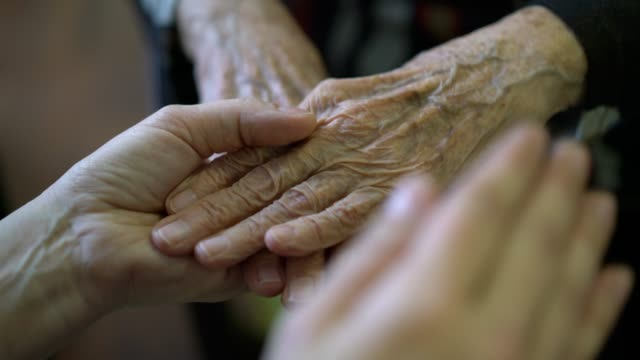 vidéos et rushes de holding elder hand, helping and giving support - affectueux