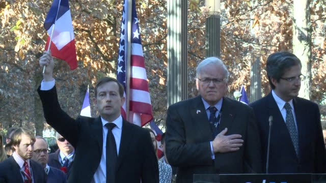 Holding French flags and roses hundreds gather at the 9/11 Memorial in New York to observe a minutes silence for the victims of the Paris attacks