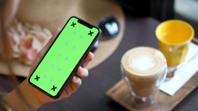 vídeos de stock, filmes e b-roll de segurando o telefone inteligente de tela verde no café - modelo web