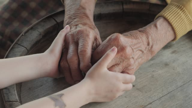 holding hands. detail of a child's hands holding the senior woman hands - multi generation family stock videos & royalty-free footage
