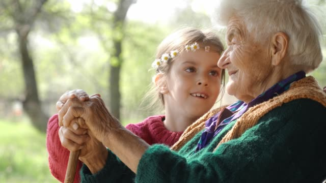 holding hands. detail of a child's hands holding the senior woman hands - dependency stock videos & royalty-free footage