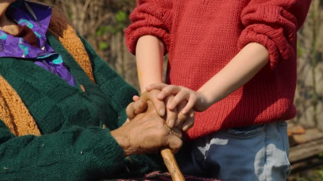 holding hands. detail of a child's hands holding the senior woman hands - childhood stock videos & royalty-free footage