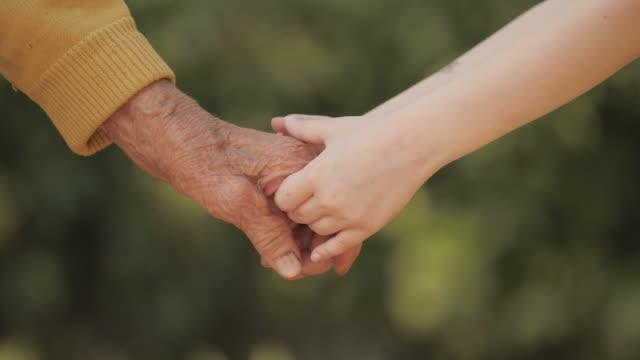 hand in hand. detail der hände des kindes senior woman händchenhalten - halten stock-videos und b-roll-filmmaterial