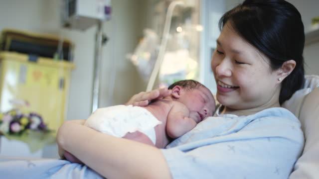 Holding Her Newborn