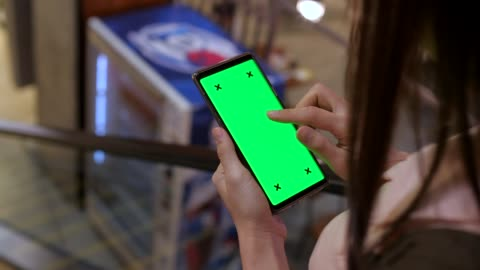 holds a smartphone with green screen on escalator - market retail space stock videos & royalty-free footage