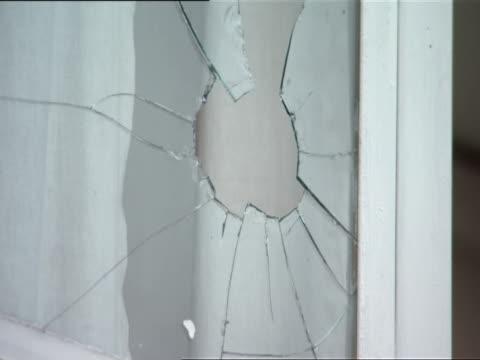 cu hole in glass of broken window in international red cross building / kigali, rwanda - キガリ点の映像素材/bロール