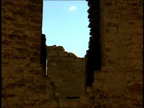 a hole is seen in a stone wall of the kin kletso archaeological site. - chaco culture national historical park stock videos & royalty-free footage
