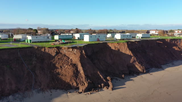 stockvideo's en b-roll-footage met holiday chalets abandoned due to coastal erosion wait to be demolished or taken by the sea in the village of withersea in the east riding of... - geërodeerd