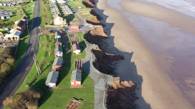 vídeos de stock, filmes e b-roll de holiday chalets abandoned due to coastal erosion wait to be demolished or taken by the sea in the village of withersea in the east riding of... - erodido