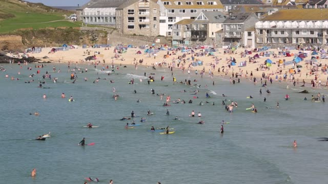 holiday makers on the beach with people surfing in st ives, cornwall, uk. - coastline stock videos & royalty-free footage