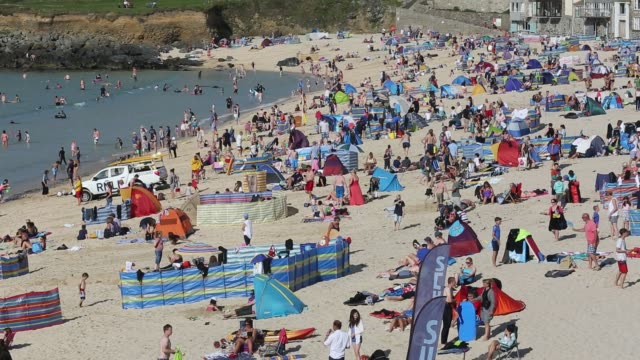 holiday makers on the beach with people surfing in st ives, cornwall, uk. - summer stock videos & royalty-free footage