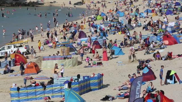 holiday makers on the beach with people surfing in st ives, cornwall, uk. - cornwall england stock videos & royalty-free footage