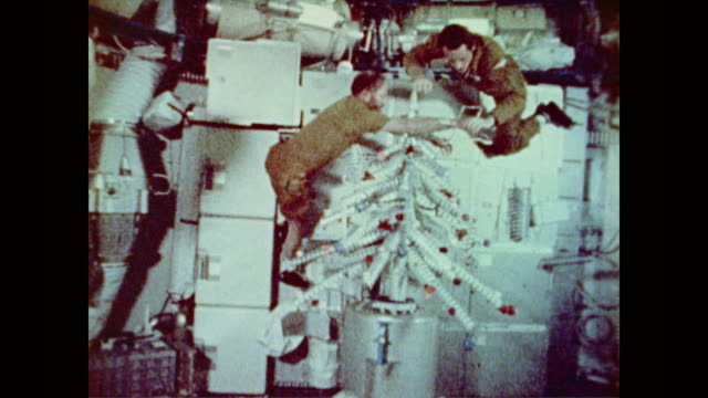 A holiday message a food can Christmas tree and simple stockings create zero gravity Christmas in space for Skylab 4 crew