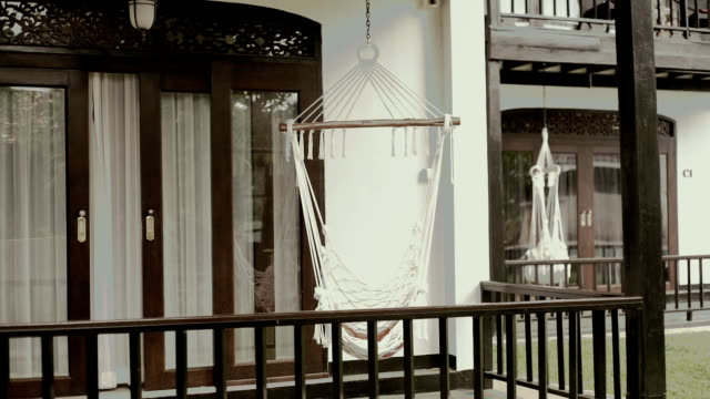 Holiday vacation, white hammock hanging on the terrace in the hotel.