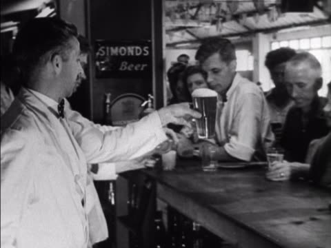 holidaymakers at the coronation holiday camp on hayling island enjoy a drink in the resorts bar. - holiday camp stock videos & royalty-free footage