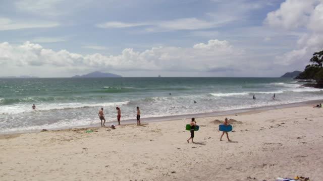 holidaymakers enjoy surf and beach - vattensport bildbanksvideor och videomaterial från bakom kulisserna