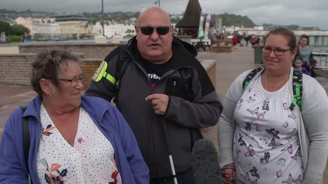 holidaymakers in south devon enjoying the great british 'staycation'; uk, devon; holiday, beach, weather, windy, steam train, railway, beach, pier,... - wet stock videos & royalty-free footage