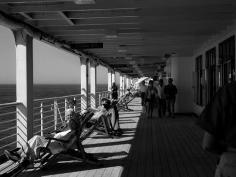 holidaymakers relax and stroll along the deck of a cruise liner - sunbathing stock videos & royalty-free footage