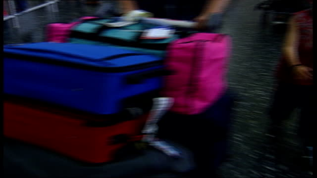 High season prices ITN ENGLAND Surrey Gatwick Airport Young boy helping to push luggage trolley thru airport PAN MS Trolley full of luggage towards...