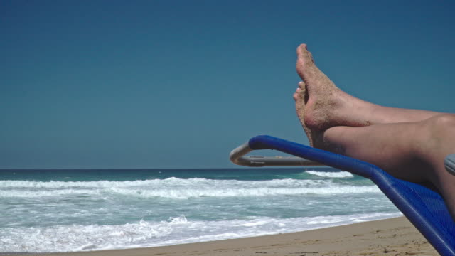 holidays on the beach - legs crossed at ankle stock videos & royalty-free footage